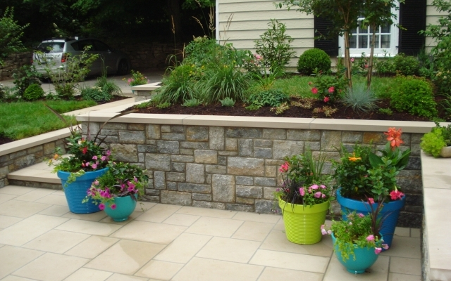 stone masonry wall with flower accent pots