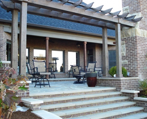 a woodwork pergola accenting a stone patio
